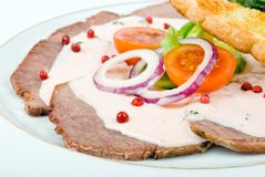 Roast meat served with vegetables over white Stock Photos