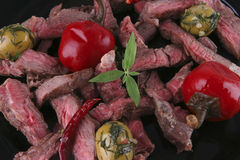Roast meat slices on black dish Stock Images