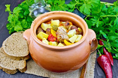 Roast meat and squash in clay pot on dark board Stock Photos