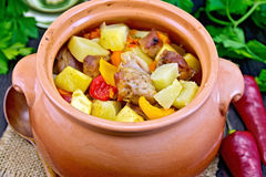 Roast meat and vegetables in clay pot on burlap Royalty Free Stock Images