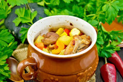 Roast meat and vegetables in pot on dark board Royalty Free Stock Photography