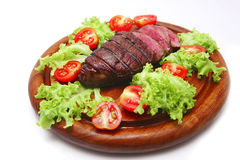 Roast meat on wooden plate with vegetables Royalty Free Stock Photos
