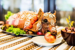 Roast pig on white plate. Decorated and roast suckling pig with an apple in his mouth on a white plate on banquet stock photography