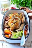 Roast pigeon with Cassoulet beans, onions, bacon, carrots, broccoli, rosemary and parsley Stock Images