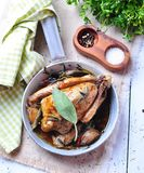 Roast pigeon with garlic, parsley, rosemary, sea salt and pepper Royalty Free Stock Images