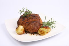 Roast pork. With some onions and rosemary on a plate Royalty Free Stock Photos