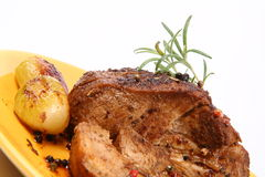 Roast pork. Decorated with some onions, rosemary and some colorful peppercorns on a yellow plate Stock Photography