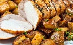 Roast Pork. Sliced Roast Pork on a plate with potatoes - close up stock photo
