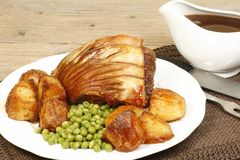 Roast pork. Shoulder joint with roast potatos peas and gravy Stock Photography