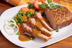 Roast pork. Close-up of a roast tenderloin pork served with vegetables royalty free stock photos