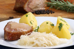 Roast pork with boiled potatoes and sauerkraut. On a plate Royalty Free Stock Photos