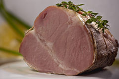 Roast pork brown. Delicious baked pork loin, decorated with tumanom Royalty Free Stock Photo