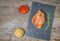 Roast pork chops with ketchup and mustard on a stone serving Board. The view from the top. Copy-space. Roast pork chop with ketchup and mustard on a stone Stock Image