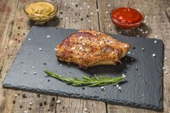 Roast pork chops with ketchup and mustard on a stone serving Board. The view from the top. Copy-space. Roast pork chop with ketchup and mustard on a stone Royalty Free Stock Images