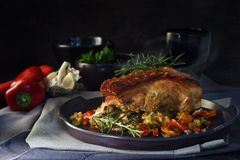 Roast pork with crust and rosemary garnish on vegetables, gray d. Ishes against a rustic dark background, moody light, copy space, selective focus, narrow depth Stock Image