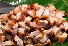 Roast pork cut into pieces on palm leaf Stock Image