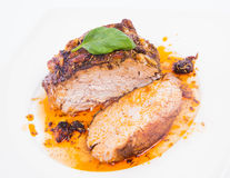 Roast pork. Decorated with basil on a white plate royalty free stock photography