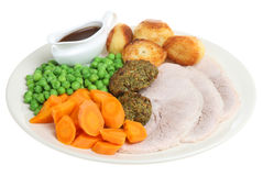 Roast Pork Dinner. With herb stuffing and individual gravy boat Royalty Free Stock Photo