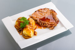 Roast pork with gravy and potatoes. On the plate Royalty Free Stock Image