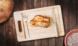 Roast pork neck on cutting board with knife and fork  on Royalty Free Stock Photos