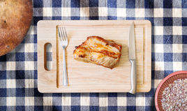 Roast pork neck on cutting board with knife and fork  on. Roast pork neck on cutting board with knife and fork on blue gingham cloth background Royalty Free Stock Images