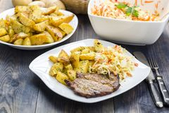 Roast pork neck served with baked potatoes. Roast pork neck served with baked potatoes and salad from fresh Chinese cabbage stock photography