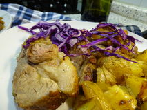Roast pork with potatoes and purple cabbage. Served on white plate with contour blurring that makes glimpse checkered cloth blue Stock Images