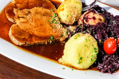 Roast pork with red cabbage and potato dumplings Royalty Free Stock Photo