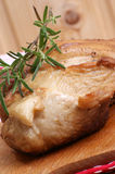 Roast pork and rosemary. Some roast pork and rosemary on a timber board Royalty Free Stock Images