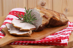 Roast pork and rosemary on a timber board. Some roast pork and rosemary on a timber board Stock Photography
