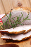 Roast pork and rosemary on a timber board. Some roast pork and rosemary on a timber board Royalty Free Stock Image