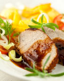 Roast pork with sauce and herbs. Closeup of roast pork with dark sauce and herbs royalty free stock photos