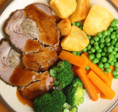 Roast Pork Sunday Dinner. Stuffed roast pork dinner with vegetables and gravy Stock Photography