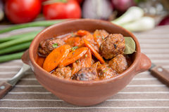 Roast in a pot with beef and vegetables. Roast in a pot with beef and carrots rustic dish Stock Photos