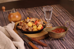Roast with a potato, meat and mushrooms and a vodka wine-glass Royalty Free Stock Image
