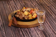 Roast with a potato, meat and mushrooms and a vodka wine-glass Royalty Free Stock Photos