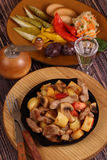 Roast with a potato, meat and mushrooms and a vodka wine-glass Stock Photo
