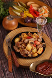 Roast with a potato, meat and mushrooms and a vodka wine-glass Stock Images