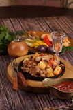 Roast with a potato, meat and mushrooms and a vodka wine-glass Royalty Free Stock Photography