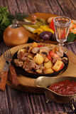 Roast with a potato, meat and mushrooms and a vodka wine-glass Royalty Free Stock Photo