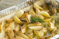 Roast potatoes. Tin of baked potatoes and flavored with rosemary Stock Photo