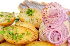Roast potatoes with hering and onion Royalty Free Stock Photos