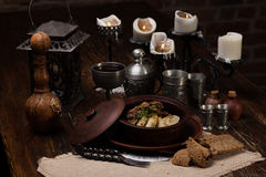 Roast potatoes with meat in pot Stock Photography