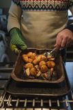 Roast Potatoes And Parsnips. Close up shot of roast potatoes and parsnips in a tray. A man is holding it and flipping the vegetables over Stock Image