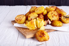 Roast potatoes seasoned with salt on wood background Royalty Free Stock Photo