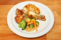 Roast poussin and vegetables. Roast poussin vegetables and gravy on a plate on a wooden tabletop Royalty Free Stock Photography