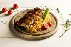 Roast ribs drizzled with sauce with stewed cabbage. On a round wooden Board Stock Image
