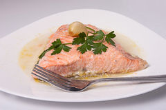Roast salmon fillet. With sauce, garlic and parsley Stock Photos