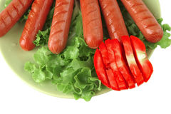 Roast sausages on green dish Royalty Free Stock Images