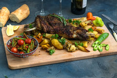 Roast shoulder of lamb on baked potato and carrots, wooden board, top view Stock Images